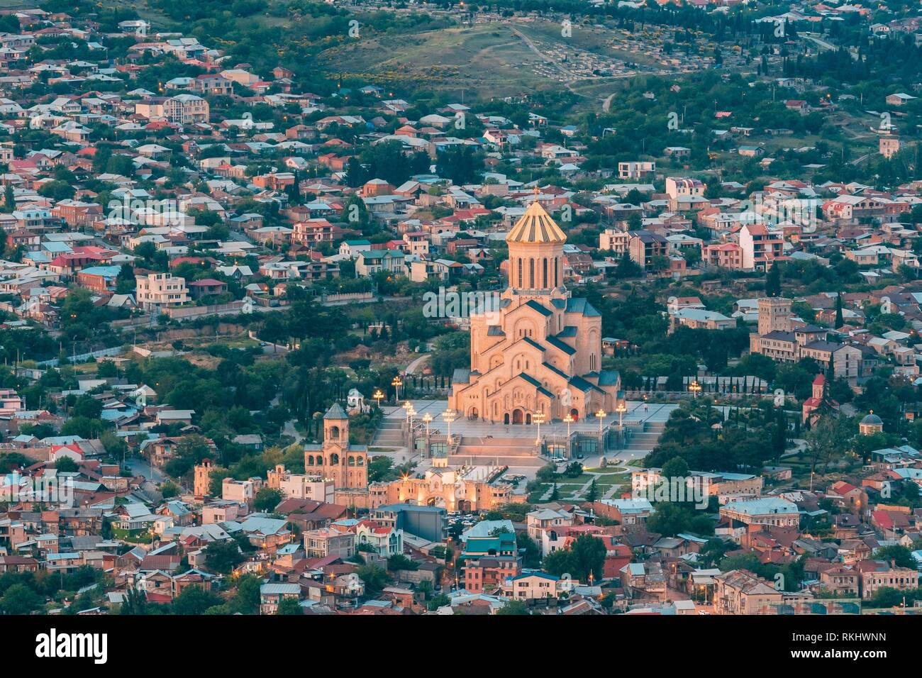 Tbilisi, Georgia. Evening Aerial Panoramic View Of Sameba Complex, Holy Trinity Cathedral Surrounded By Populous Residential Area In Summer Dusk. Stock Photo