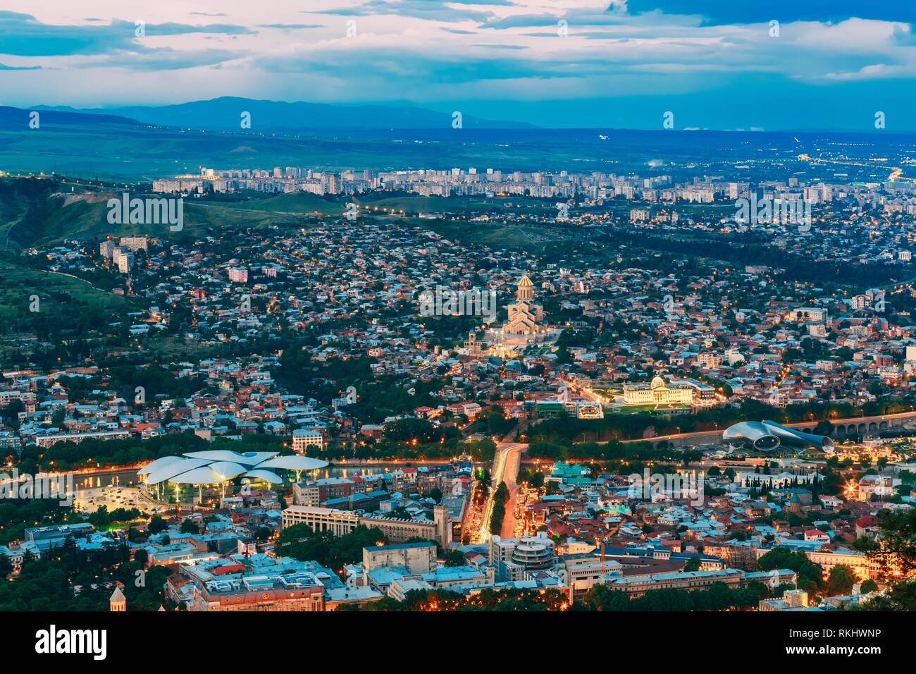 Tbilisi, Georgia. Evening Scenic Aerial Cityscape With All Famous Landmarks In Bright Illumination In Summer Twilight, Blue Cloudy Sky Under Dark Stock Photo