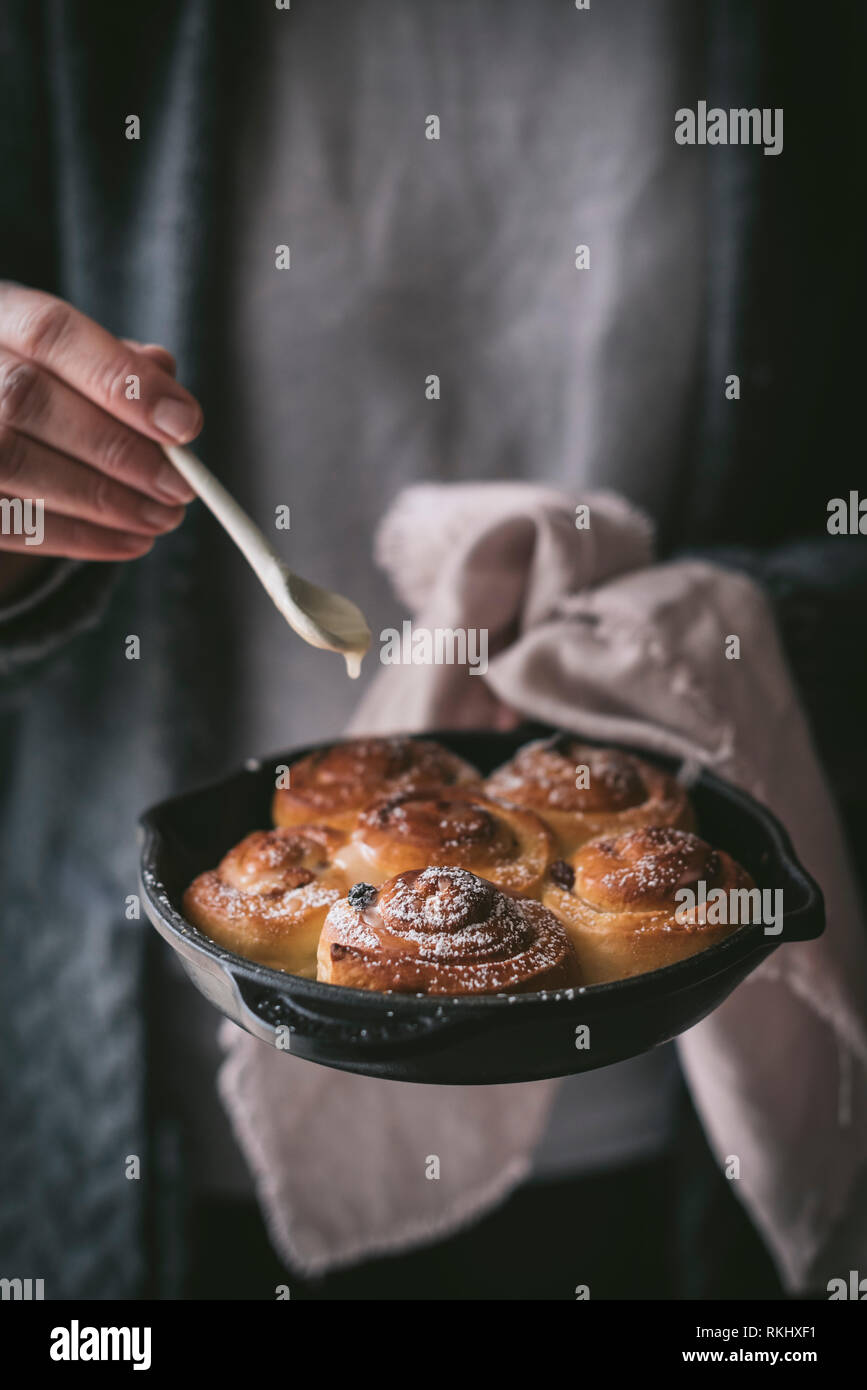 Unrecognizable female with small spoon adding sweet sauce to delicious fresh cinnamon rolls on frying pan - Stock Image