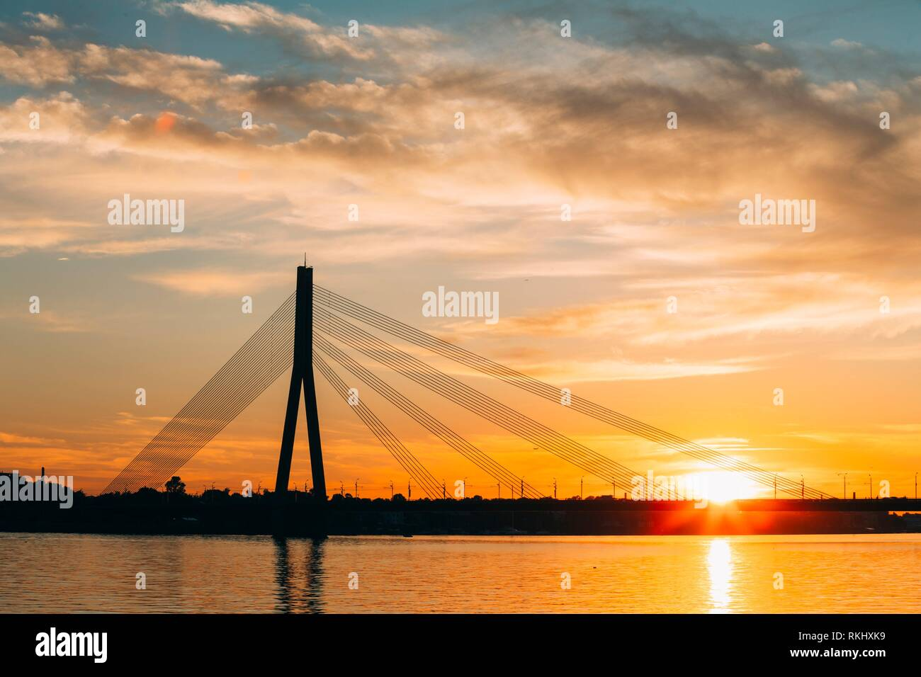 Riga, Latvia. Scenic View Of Vansu Cable-Stayed Bridge Over The Daugava River, Western Dvina In Bright Sunset Or Sunrise Time. Stock Photo