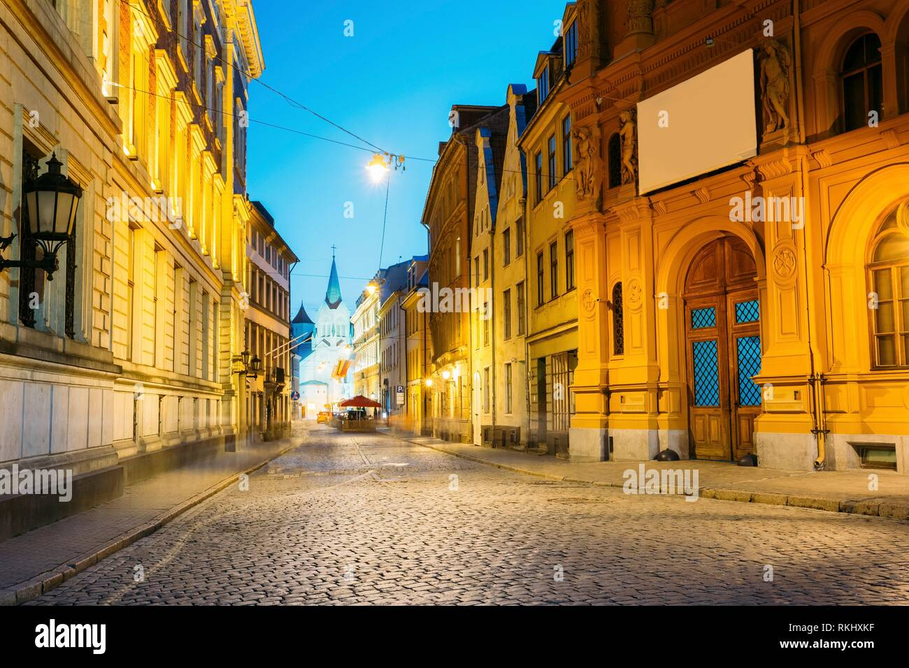 Riga, Latvia. Evening View Of Deserted Pils Street With Ancient Architecture In Bright Warm Yellow Illumination Under Summer Blue Sky. Our Lady Of - Stock Image