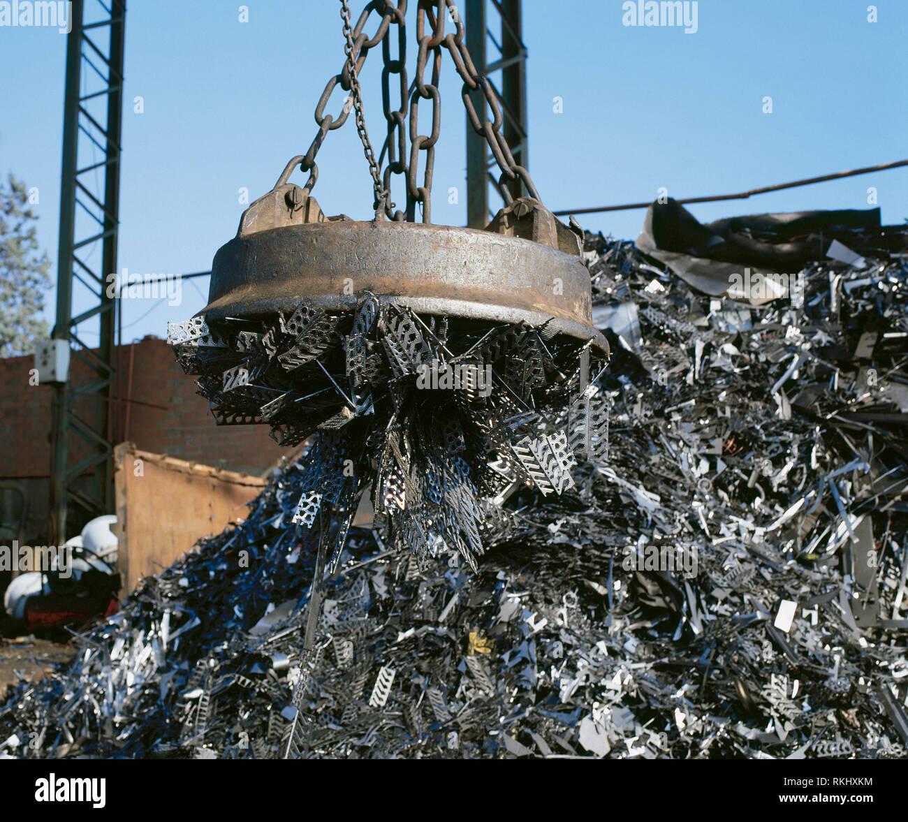 Electromagnet on crane lifting metal at scrap yard. Stock Photo