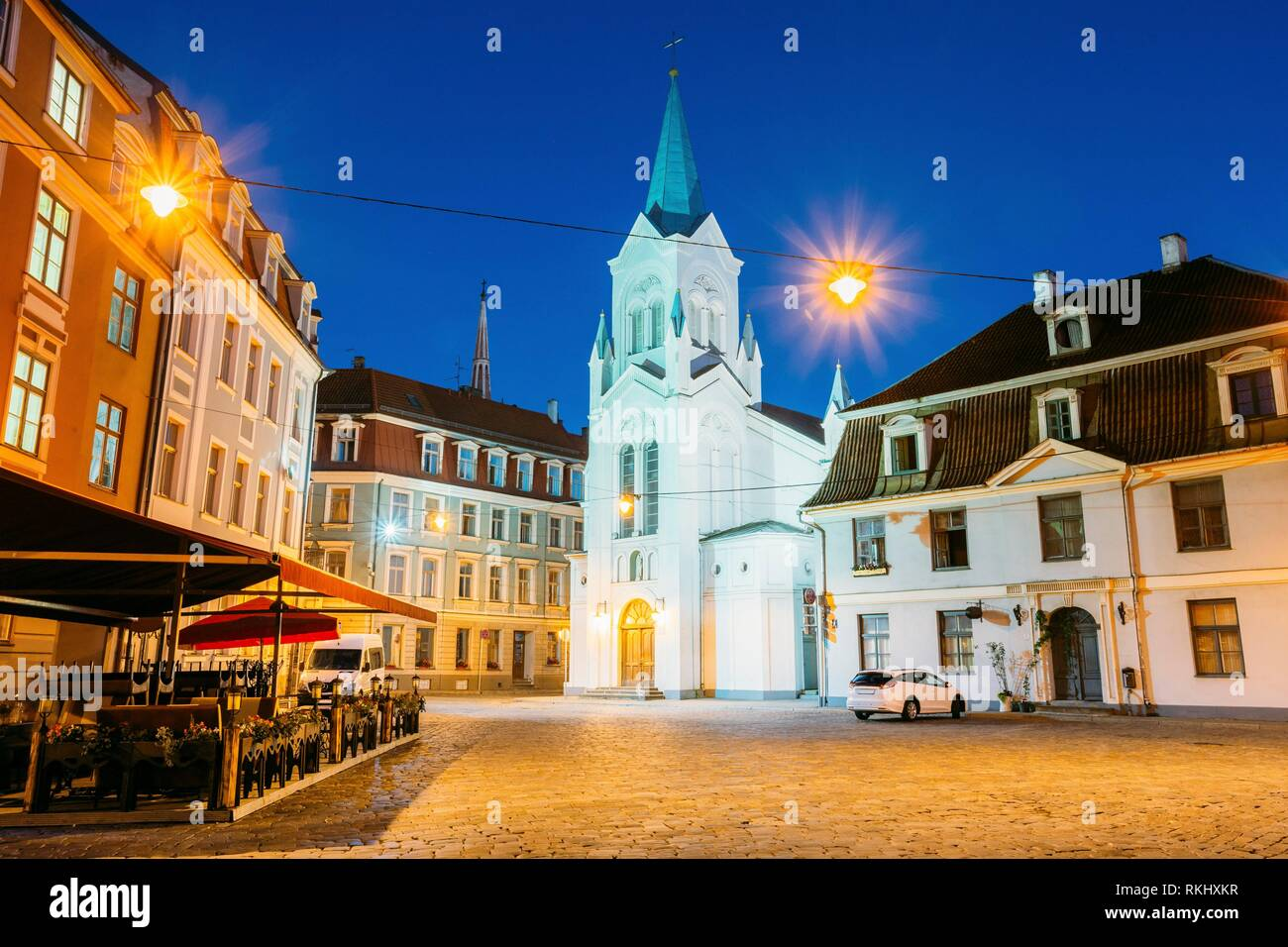Riga Latvia. Main Facade Of Virgin Of Anguish Or Our Lady Of Sorrows Church, Ancient Catholic Church On Pils Street In Evening Illumination In Summer - Stock Image