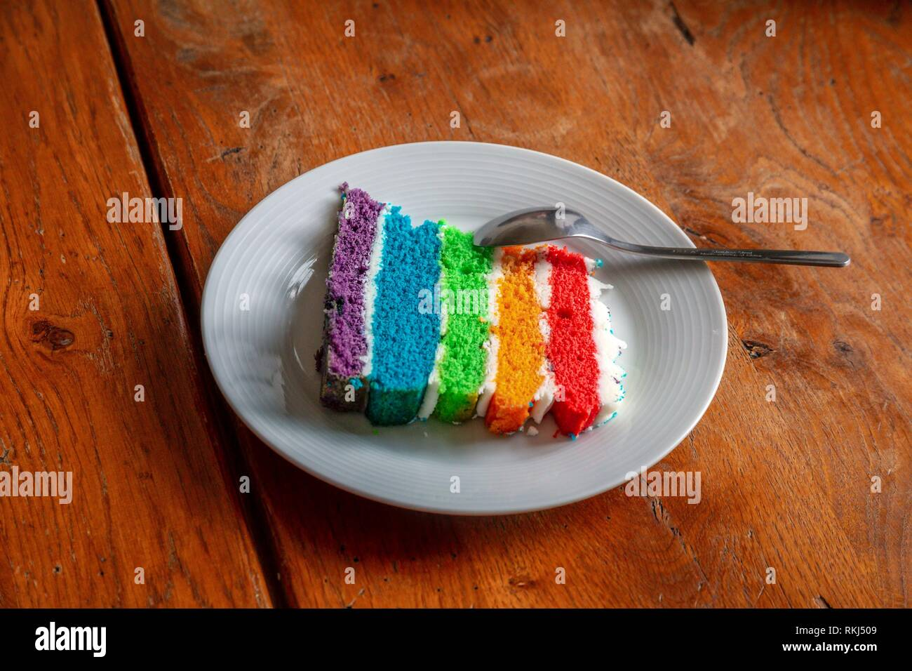 A slice of multi layered rainbow cake. - Stock Image