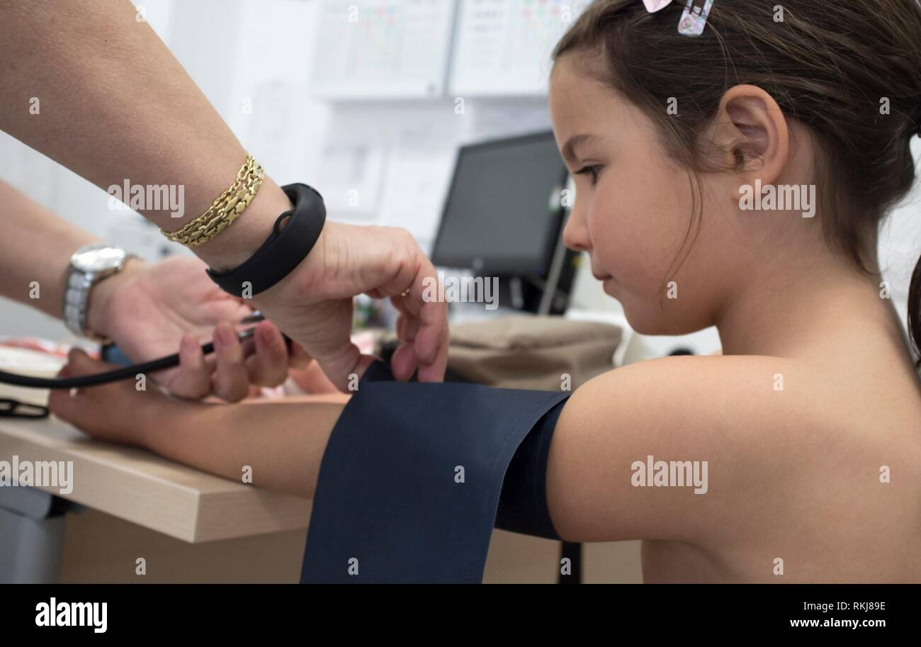 Little girl being giving blood pressure test doctor. Periodical pediatric review concept. - Stock Image