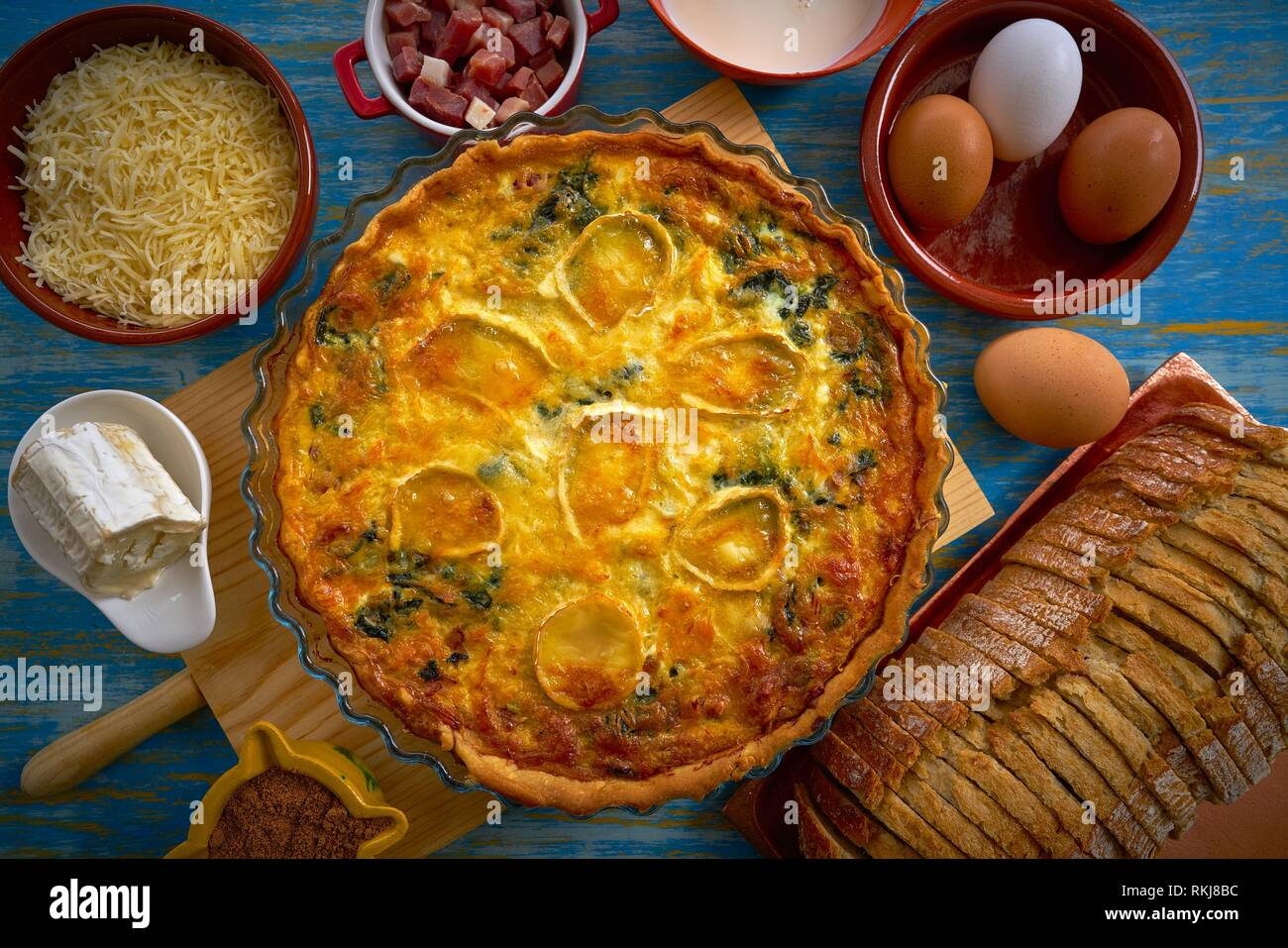 Quiche recipe with spinach and goats cheese on blue table. - Stock Image
