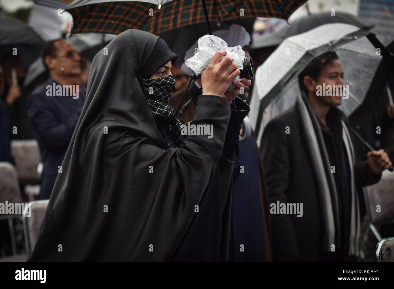 An Iranian photographer girl is shooting at 40th anniversary of Iranian revolution victory. Iranians attend a ceremony celebrating the 40th anniversary of their Islamic Revolution, Shiraz city in Fars province, Iran, Monday. Feb. 11, 2019. Hundreds of thousands of people poured out onto the streets of Shiraz and other cities, towns and provinces across Iran, marking the date 40 years ago that is considered as victory day in the country's 1979 Islamic revolution. - Stock Image