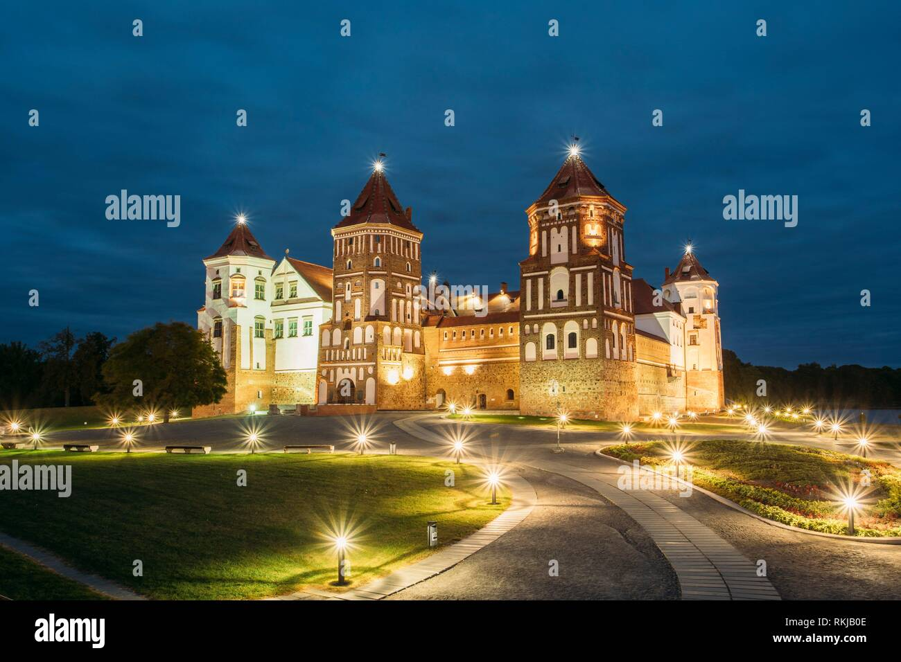 Mir, Belarus. Mir Castle Complex In Evening Illumination Lighting. Famous Landmark, Ancient Gothic Monument Of Feudalism Under Blue Night Sky. UNESCO - Stock Image