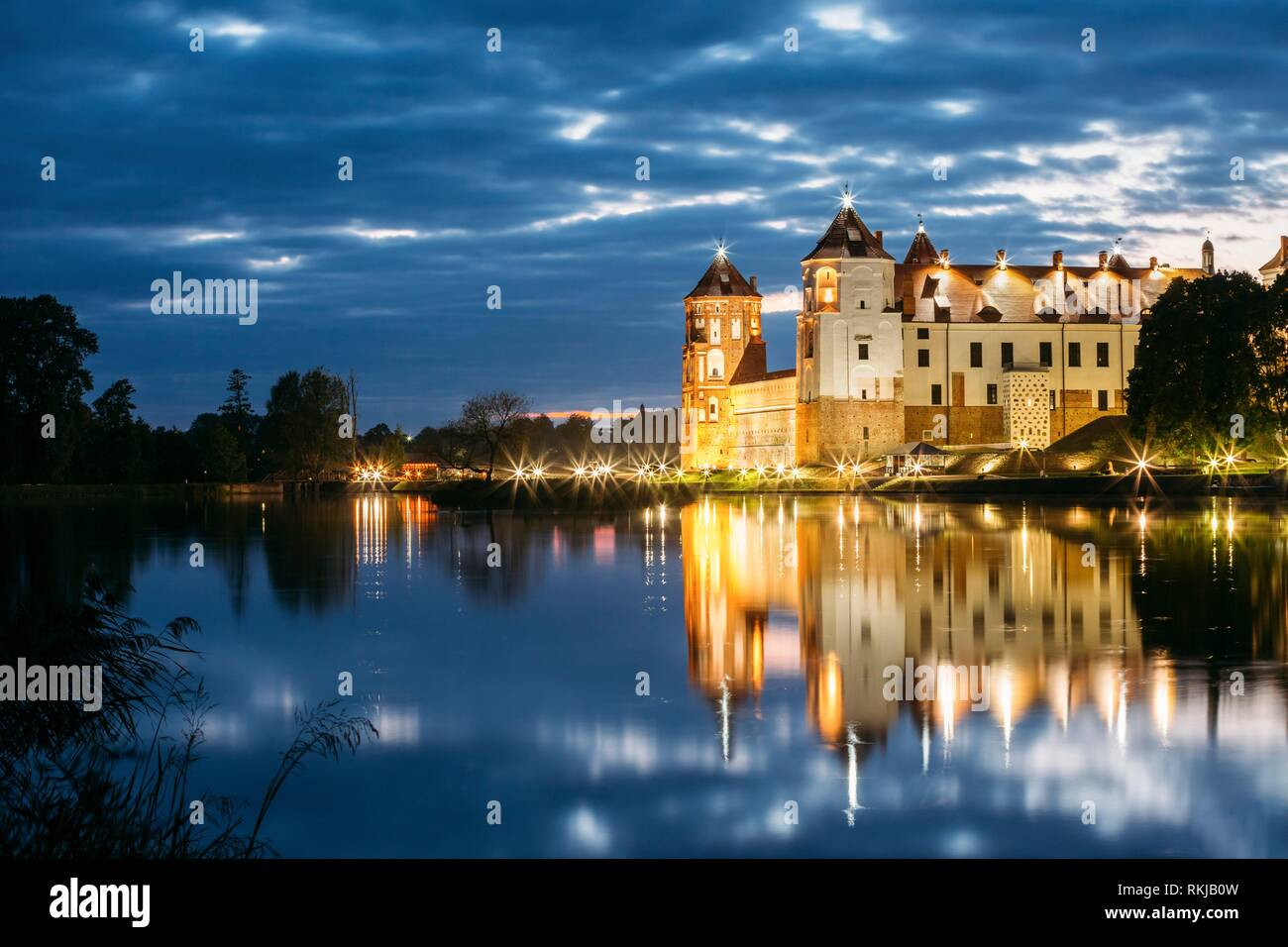 Mir, Belarus. Mir Castle Complex In Bright Evening Illumination With Glow Reflections On Lake Water. Famous Landmark, Ancient Gothic Monument Of - Stock Image