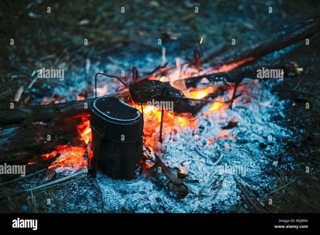 Food Is Cooked Over A Fire In An Old Vintage Retro Marching Pot Dixie. German Wehrmacht Infantry Soldier's Military Equipment Of World War II. - Stock Image