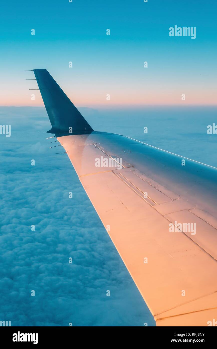Sky View From Airplane Window. Window Seen Beautiful Sunset Sunrise From Height Of Airplane, Plane. Bright Blue, Orange And Yellow Colors Of Sunrise - Stock Image