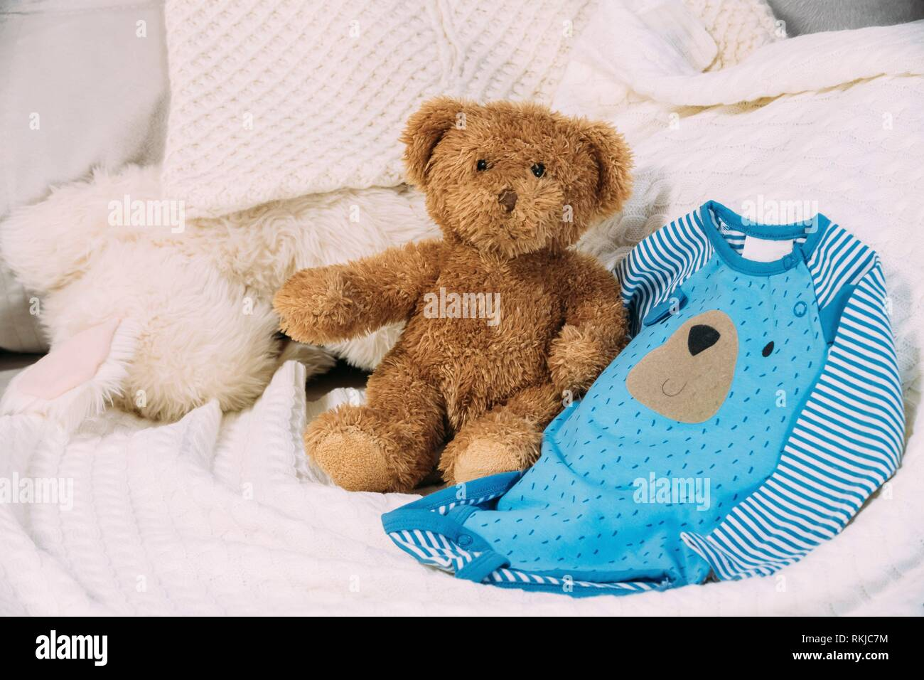 Funny Soft Toy Teddy Bear Near Child's Baby Clothes Rompers. - Stock Image