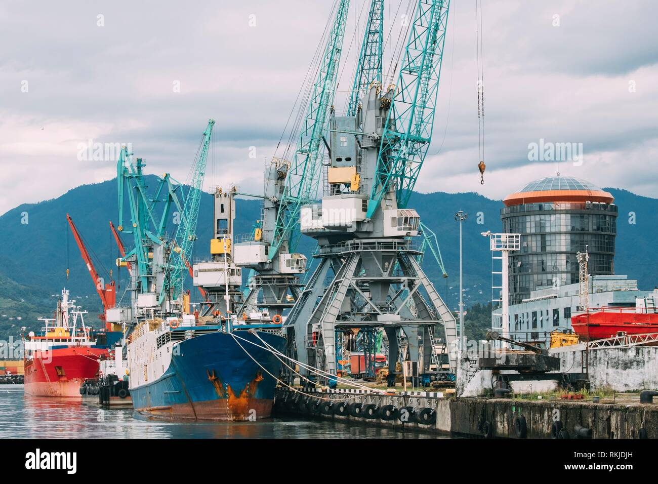 Batumi, Adjara, Georgia. Old Barge Freight Ship Tanker And Heavy Loading Cranes Jib In Port Dock. - Stock Image
