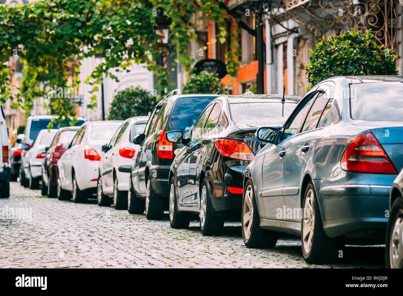 Many Cars Parked On Street In European City In Sunny Summer Day. Row Of City Cars. - Stock Photo