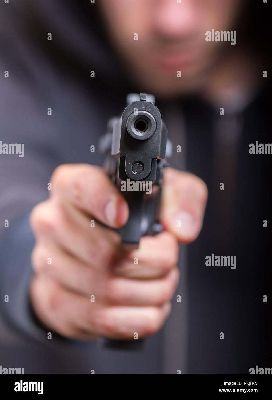 Man with gun, gangster, focus on the gun. - Stock Image