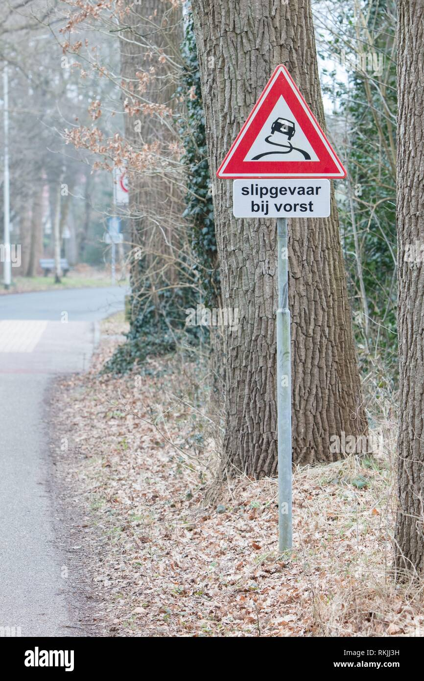 Road sign warning against slippery road due to snow ice (dutch). - Stock Image