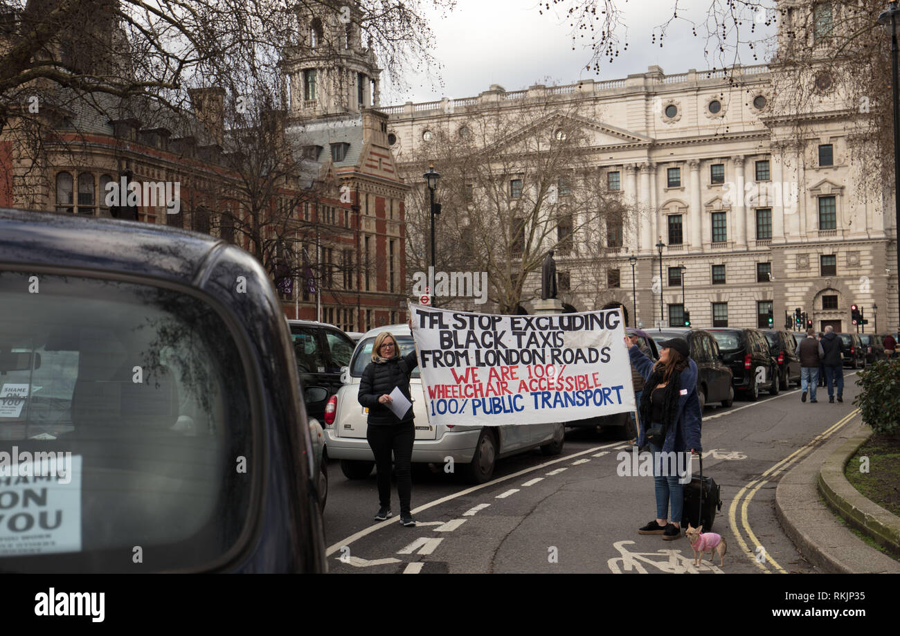 London, UK. 11th February 2019. To female supporters hold a banner in support of the licensed taxi drivers, who bring traffic to stand still around Parliament Square, Westminster, London, today, protesting against policies of the Transport for London (TfL) and Mayor Khan. Credit: Joe Kuis / Alamy Live News Stock Photo