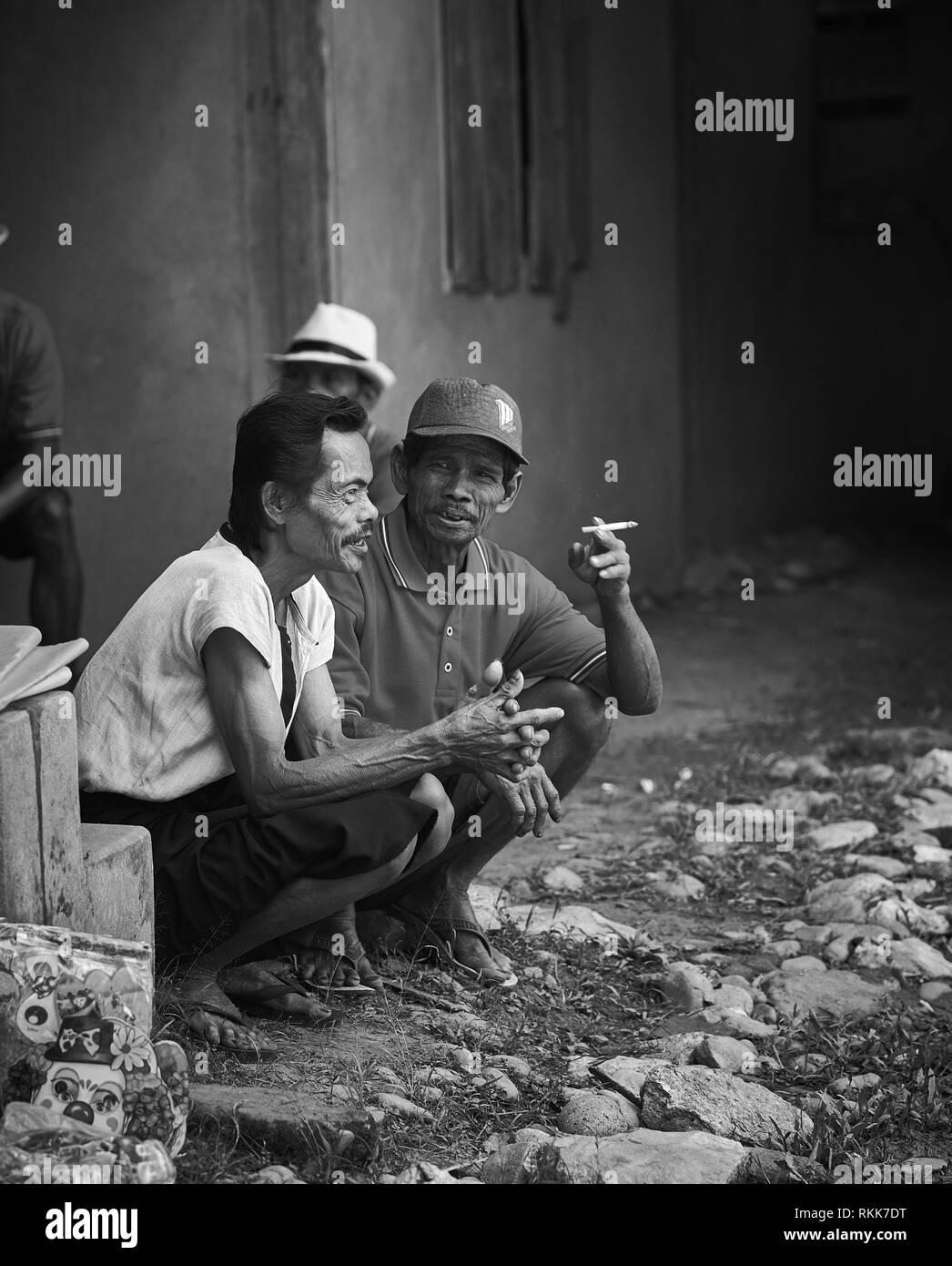 Indonesian people speaking while smoking - Stock Image