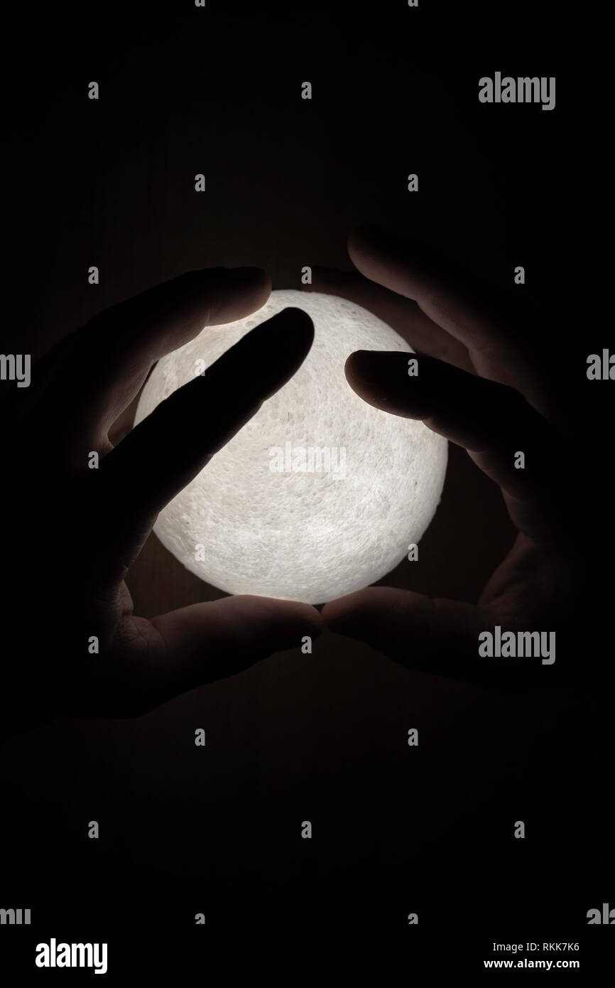 Small moon light in mans hands Stock Photo