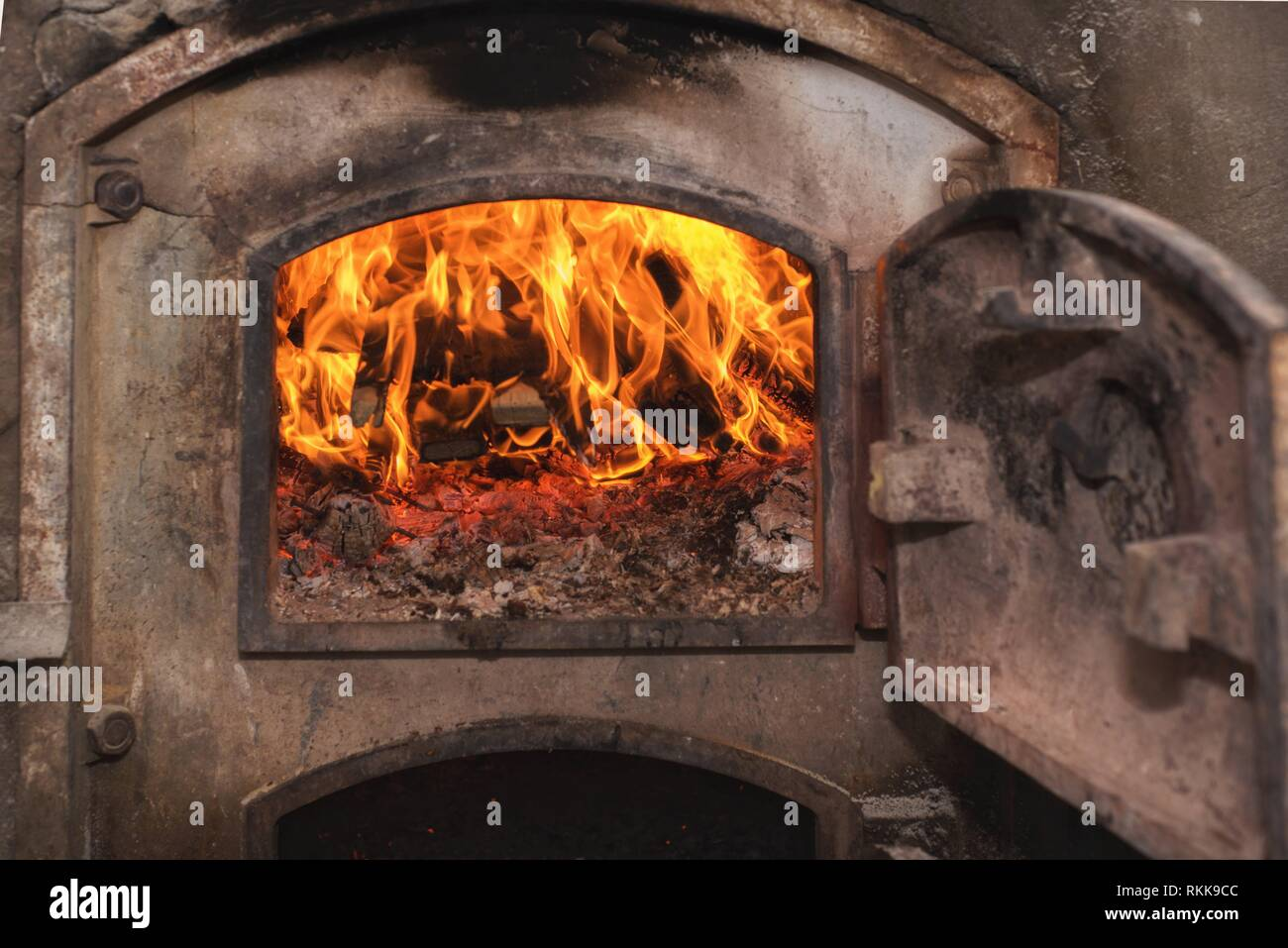 Fire wood in ancient rust stove. - Stock Image