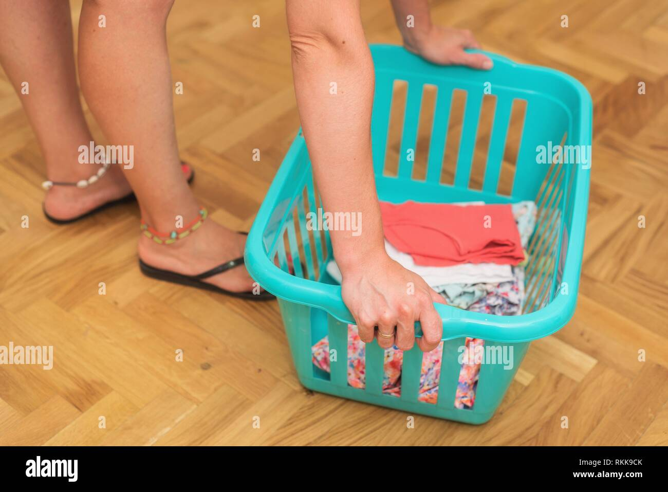Young woman doing housework holding a basket with laundry. - Stock Image