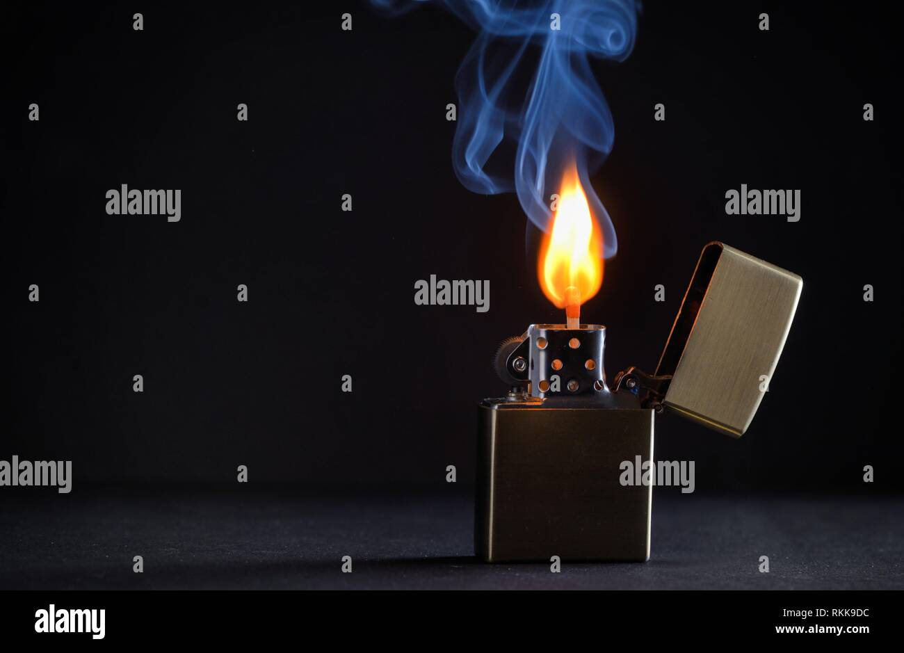 Concept golden metal lighter and smoke. - Stock Image