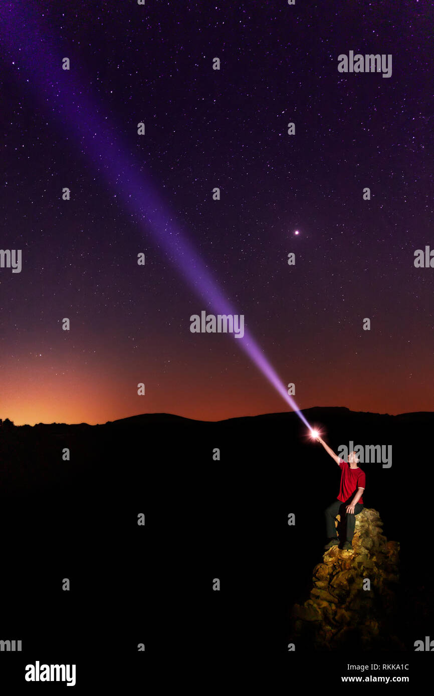 A sitting man pointing to a starry sky with a flashlight. - Stock Image