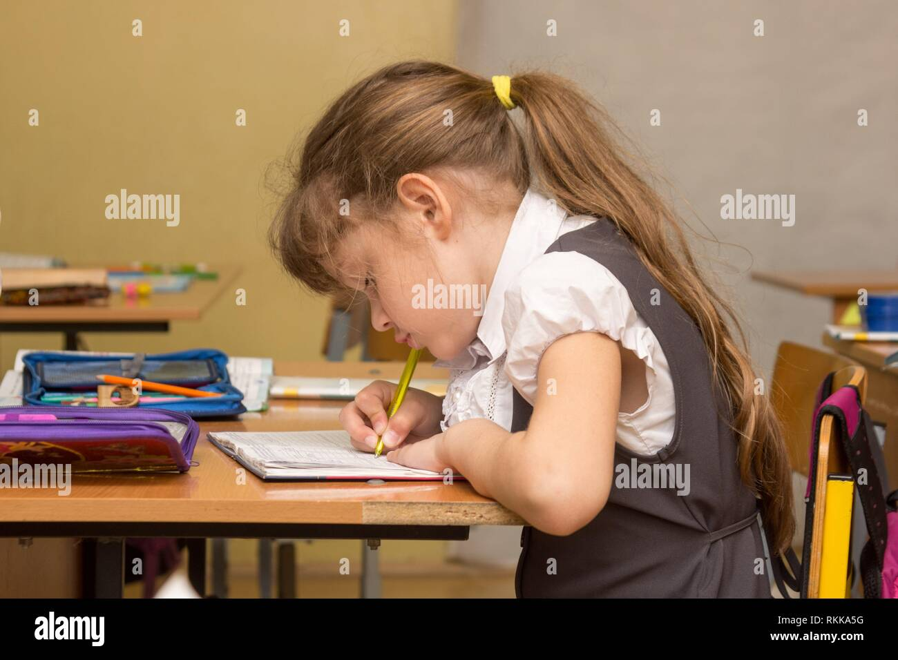 A schoolgirl in a lesson crouched writes in a notebook. Stock Photo