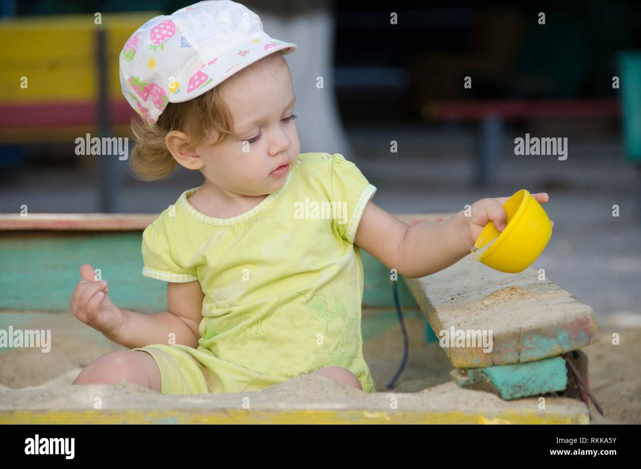 Little girl is playing in the old sandbox. - Stock Image