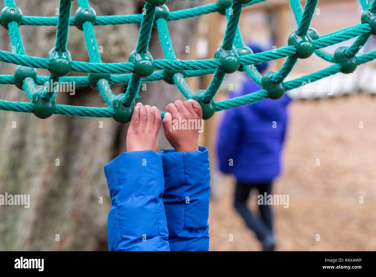 A young child hanging onto rope climbing equipment in Battersea Park, London. - Stock Image