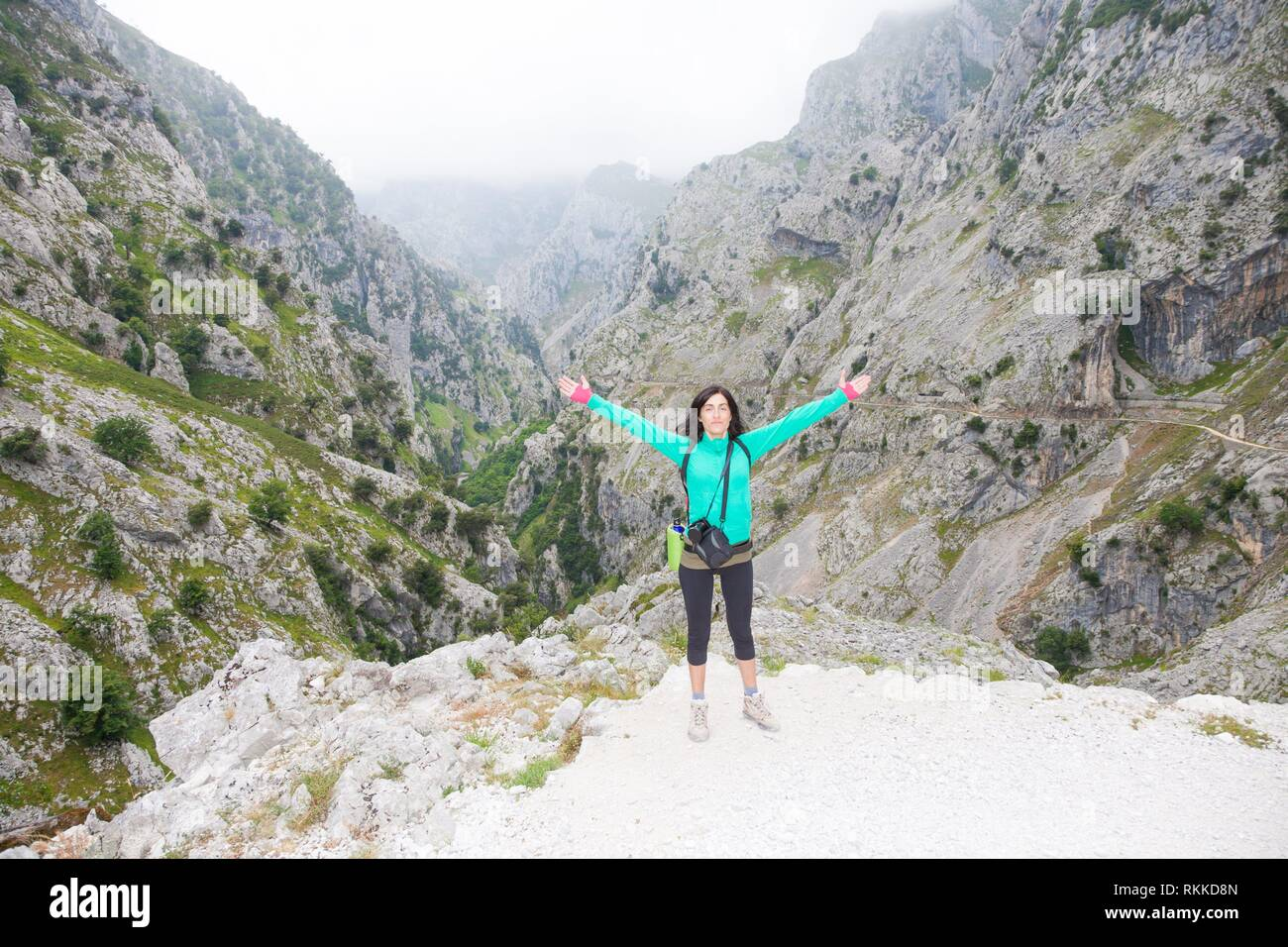 brunette sport hiking or trekking woman with open arms outstretching posing looking at Gorge of Cares River, in mountain Picos de Europa natural park - Stock Image