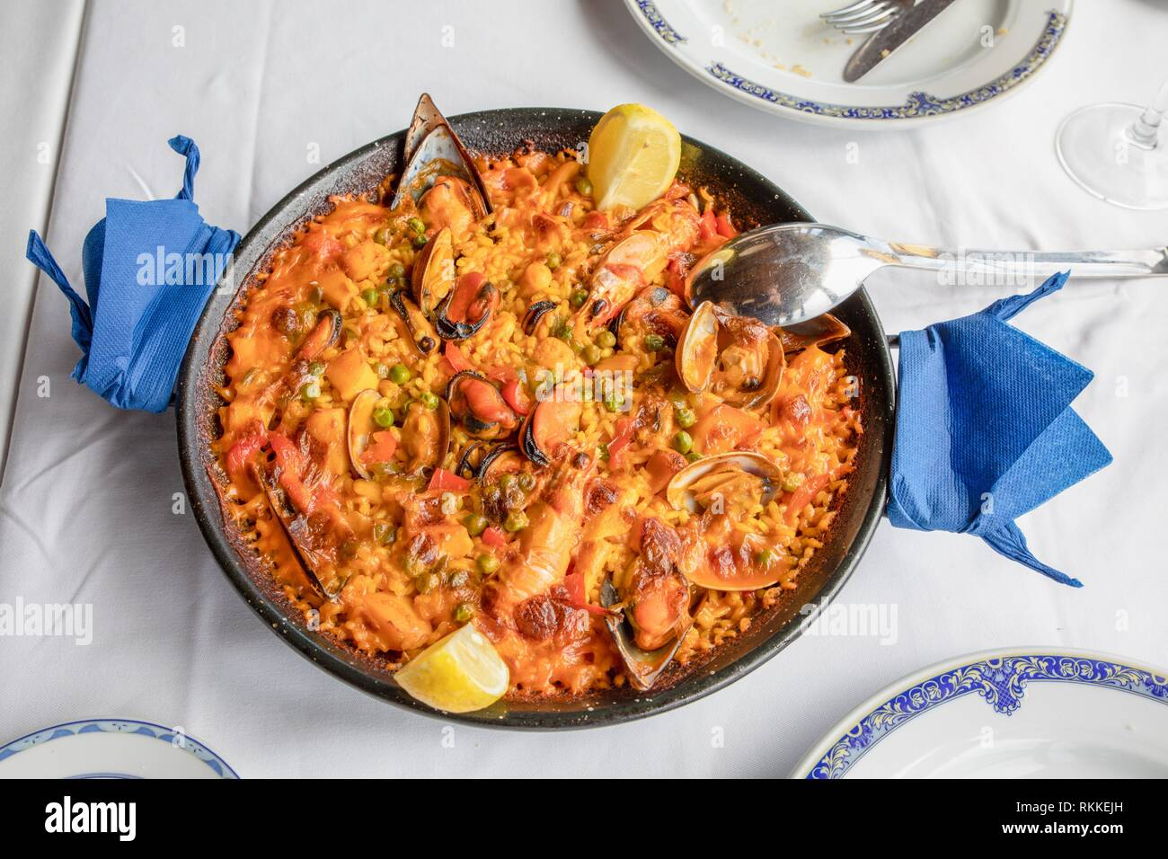 above view of typical Spanish paella with seafood (mussel, prawn, lobster, squid, clam), rice and lemon ready to serve on white tablecloth of Stock Photo