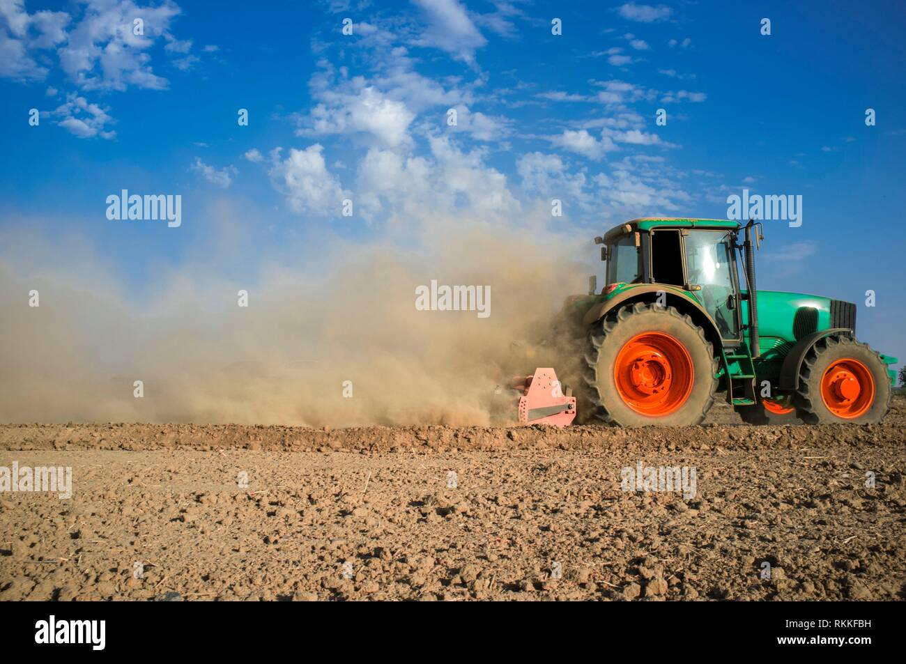 Farm tractor preparing dusty soil affected by drought. Drought and agriculture concept. Spain. - Stock Image