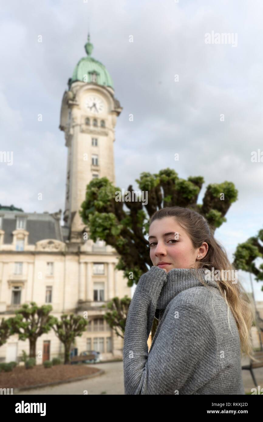 Teenager looking at camera in front of the Limoges station in France. - Stock Image