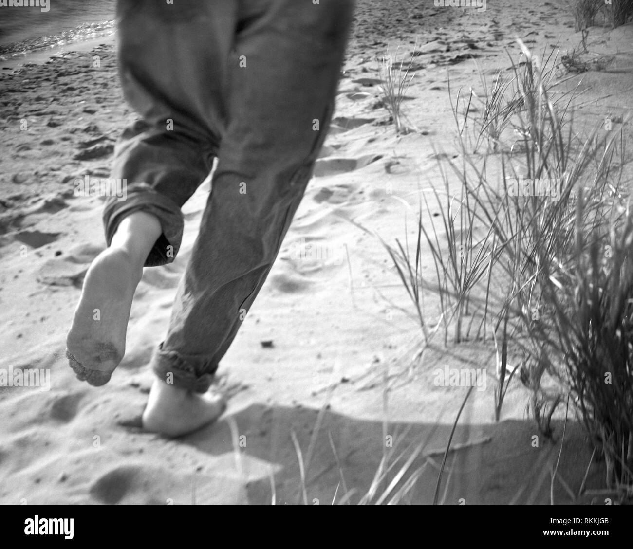 Man with rolled up pants running on sand at beach. - Stock Image