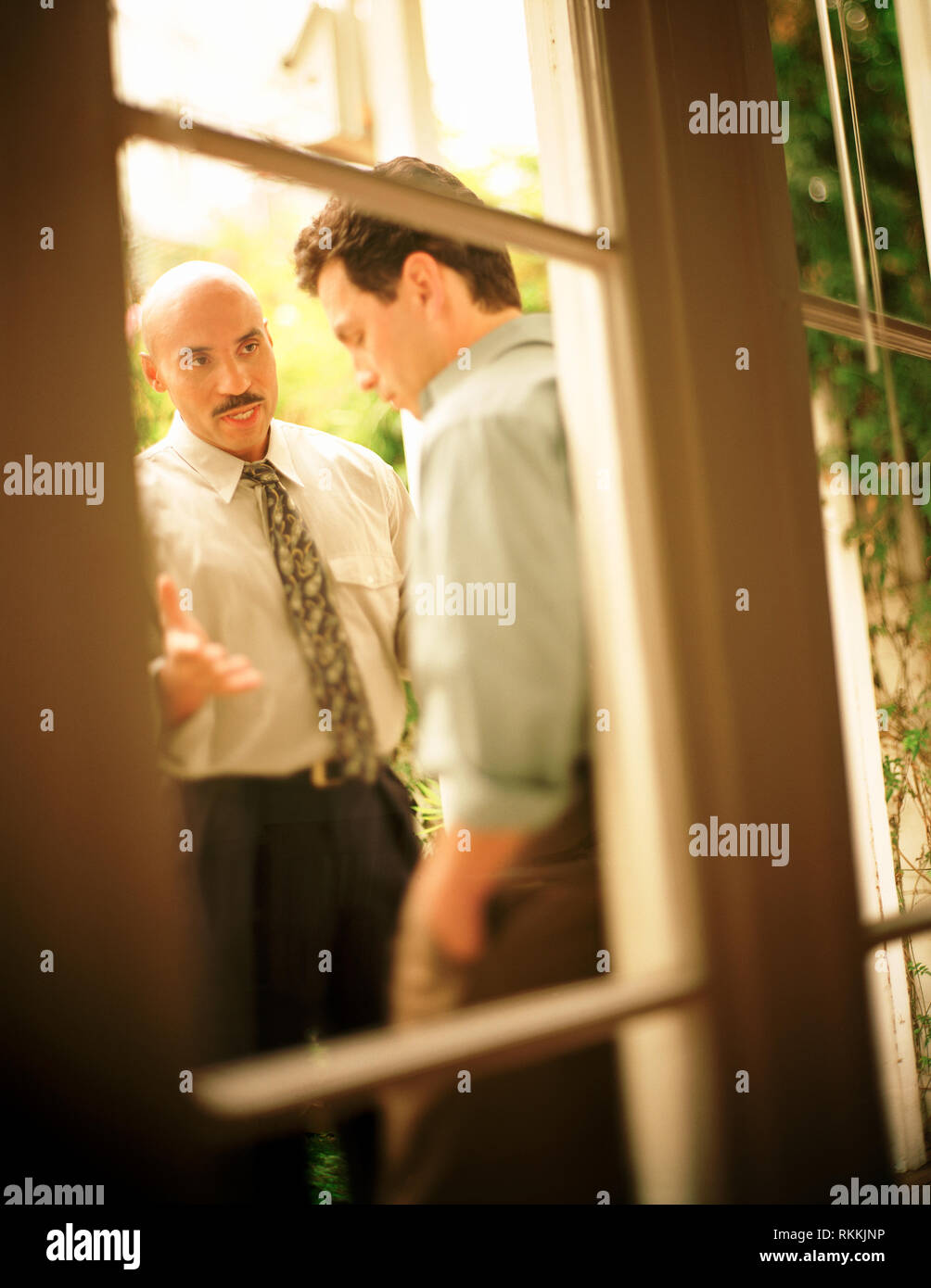 Side view of two men engaged in a serious discussion. - Stock Image