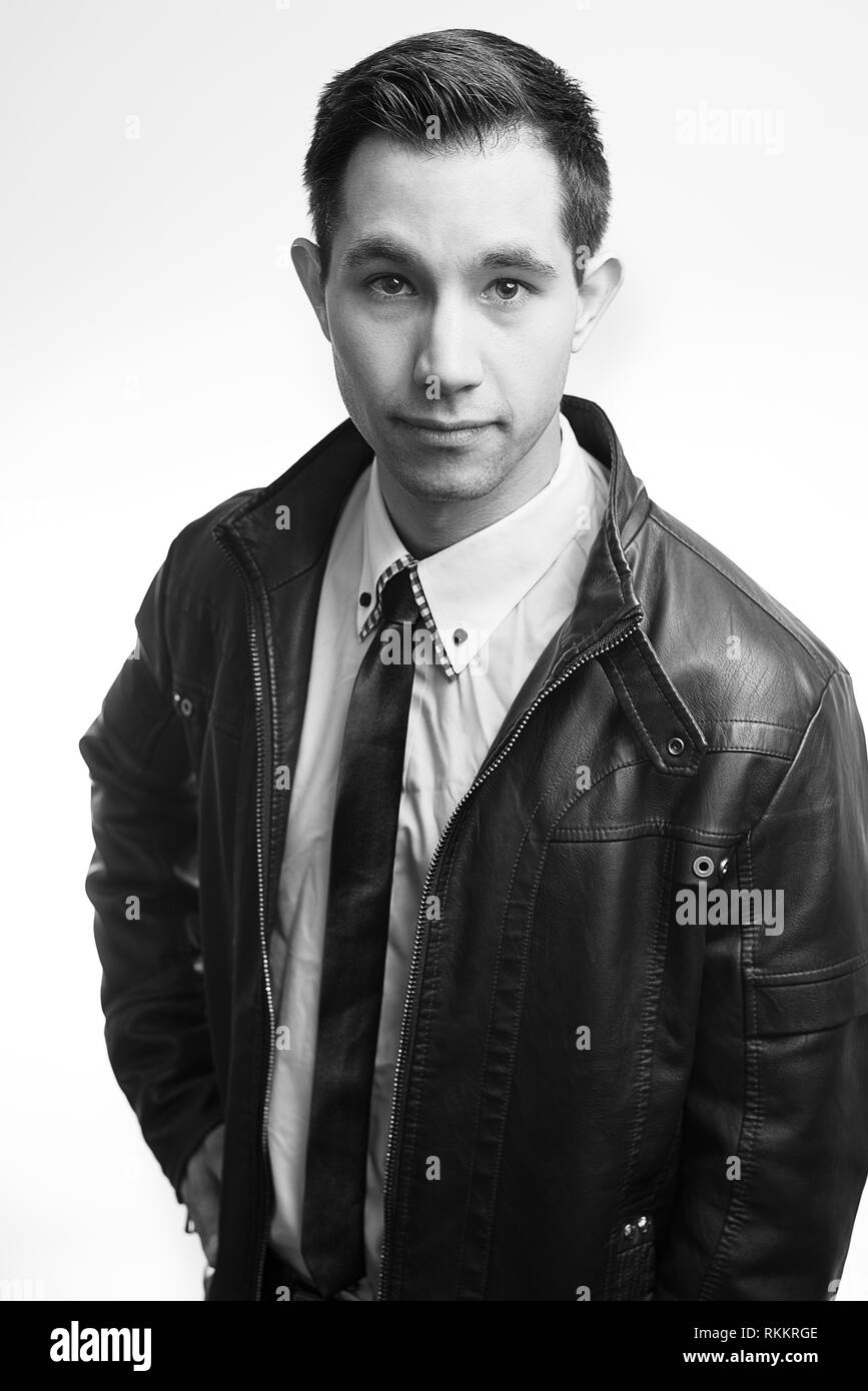 Young man in leather jacket and tie looking at camera with serious look, Maine, USA - Stock Image
