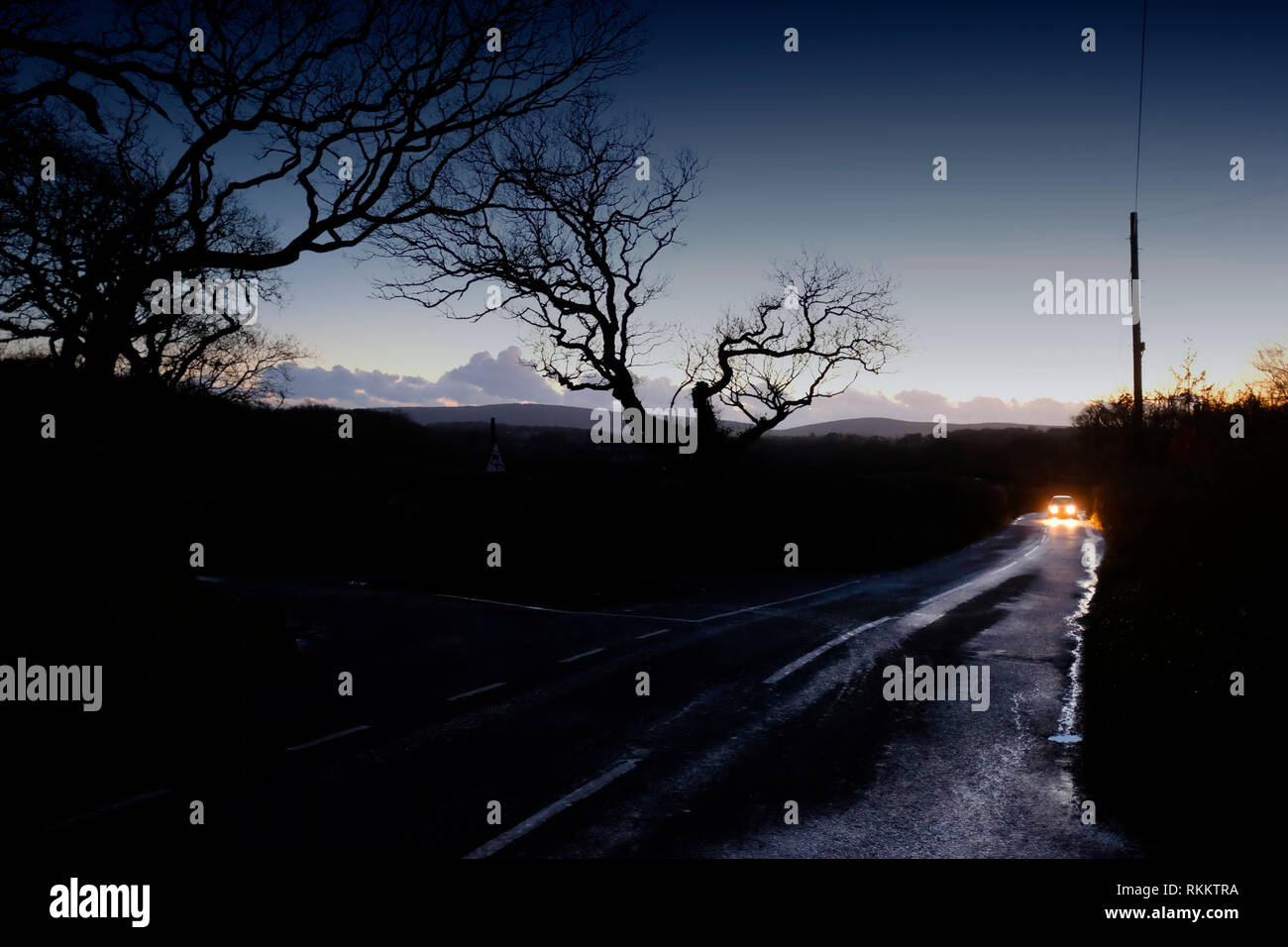 Car driving fast along country road at dusk, night, on wet road, after rain storm, headlights on, bright, slippery road conditions, rural driving. - Stock Image