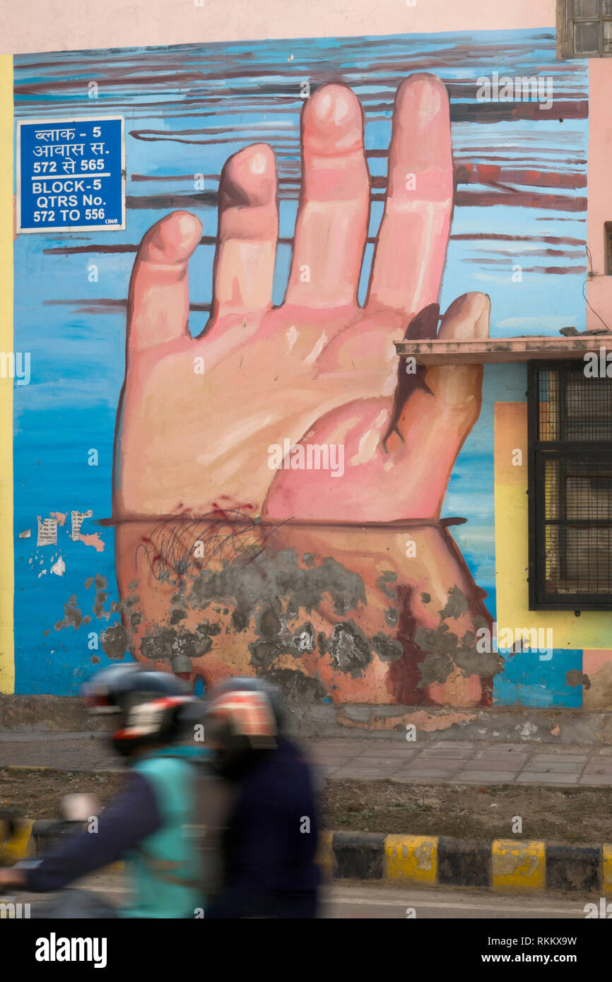 A couple on motorbike pass a mural titled Hands Underwater by artist Gaia, in Lodhi Colony, New Delhi, India - Stock Image
