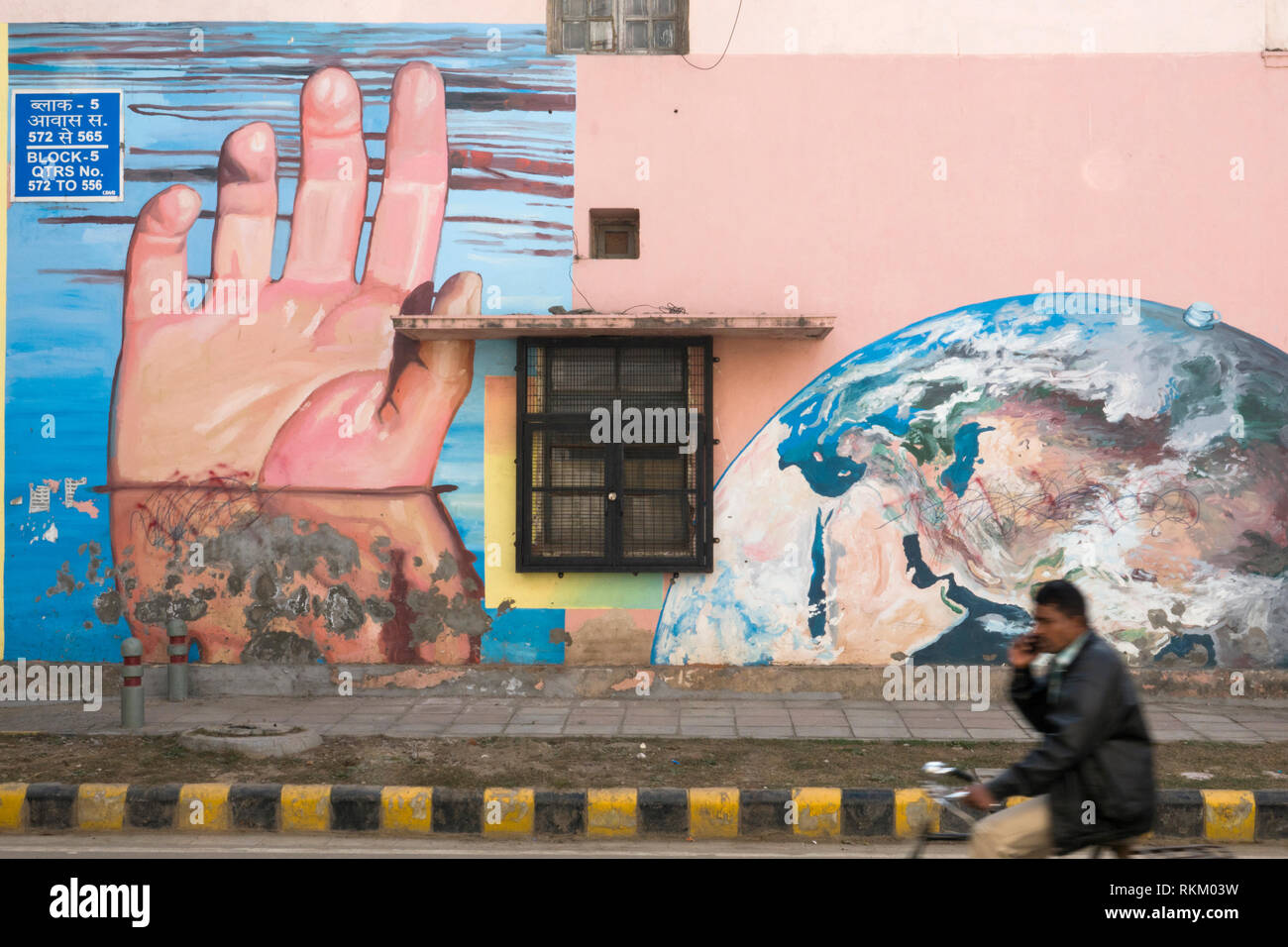 Man rides past a mural titled Hands Underwater by artist Gaia, in Lodhi Colony, New Delhi, India - Stock Image