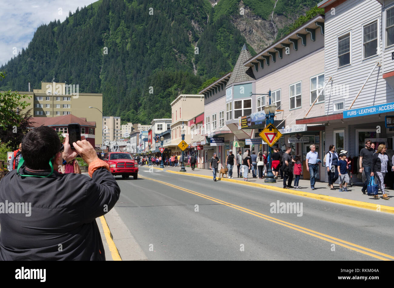 Person uses smartphone to photograph the downtown tourist area of Juneau, Alaska. - Stock Image