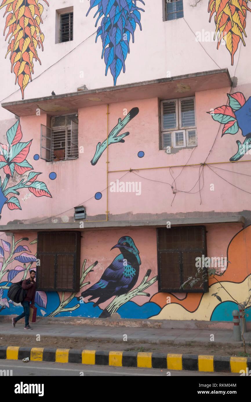 A man walks past a mural by Brazilian artists Bicicleta Sem Freio, in Lodhi Colony, New Delhi, India - Stock Image