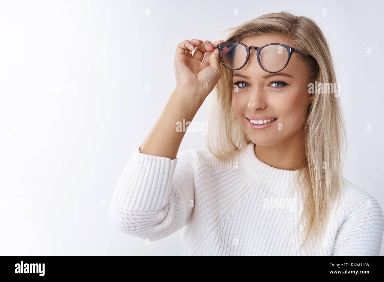 Close-up shot of attractive young and happy european female in sweater taking off glasses looking delighted with pure upbeat smile promoting eyewear - Stock Image