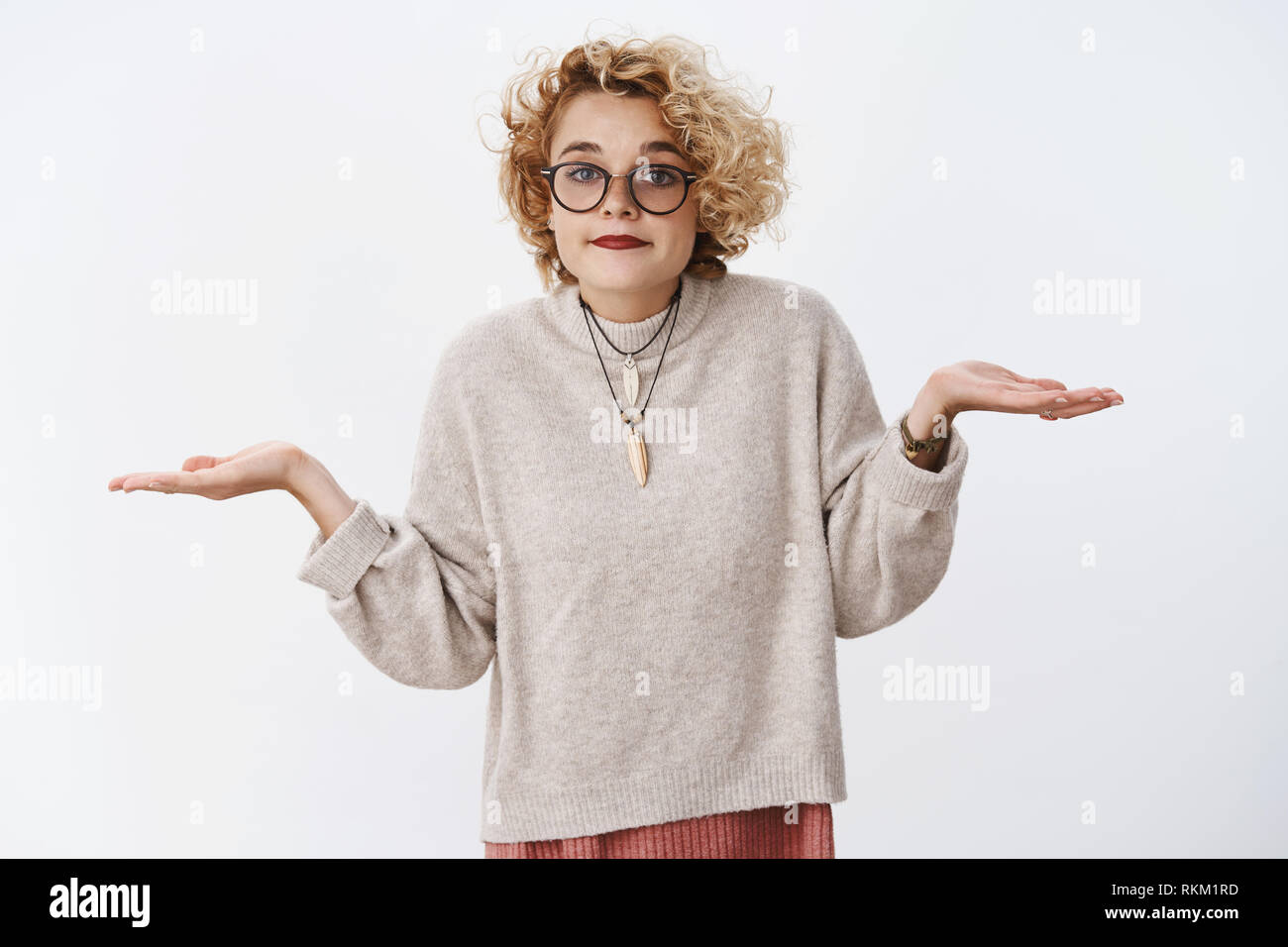 Well there nothing we can do about it. Portrait of unbothered and clueless cute european blond female coworker shrugging with hands spread sideways - Stock Image