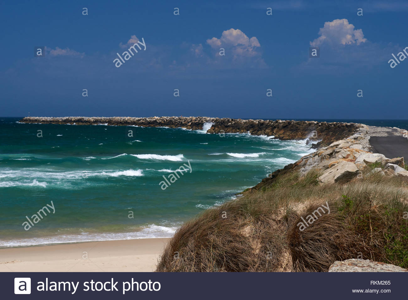 The long break wall - the 'North Wall' - at Iluka; protecting the entrance to the Clarence River. The Pacific Ocean, blue skies with clouds as well. - Stock Image