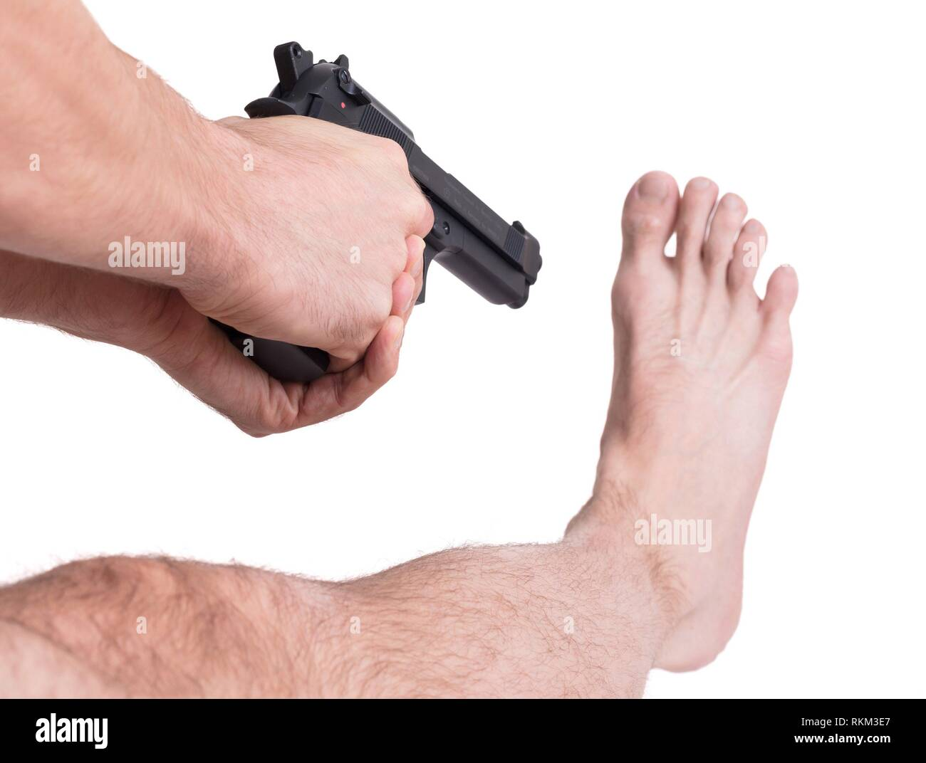 Concept - Man shooting himself in the foot. - Stock Image