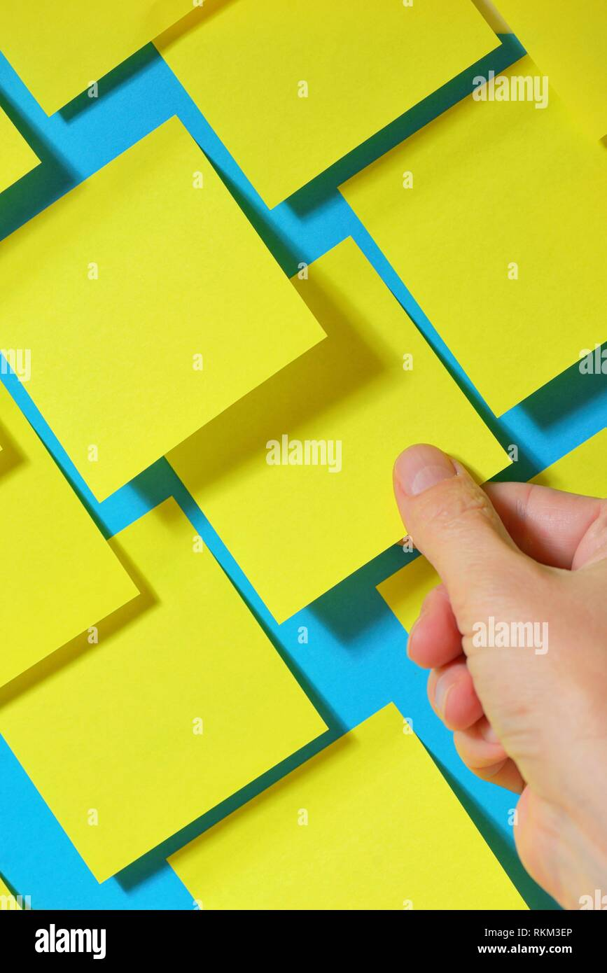 Hand holding post-it note on board. - Stock Image