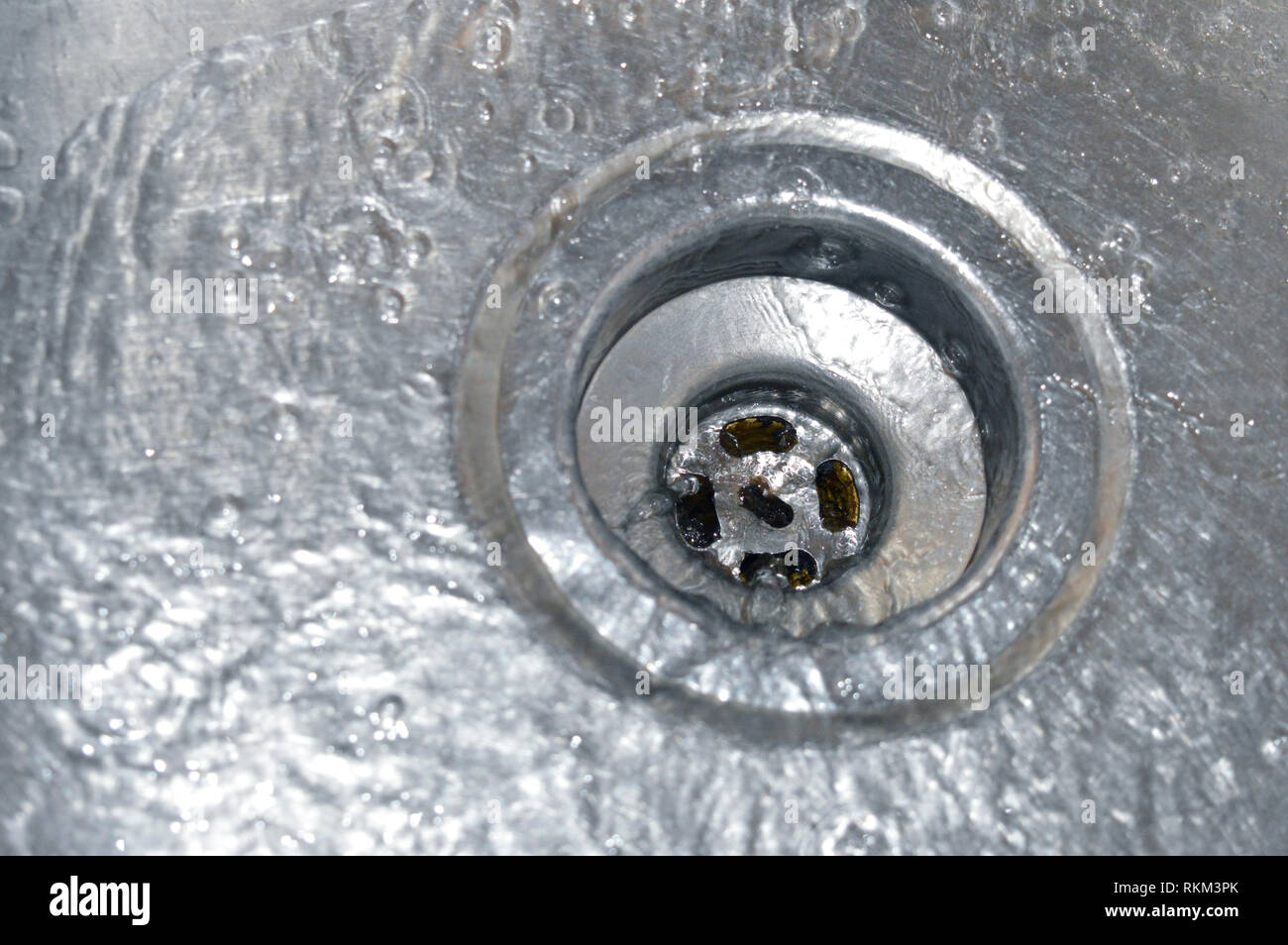 fast running water flowing down a kitchen or bathroom drain Stock Photo