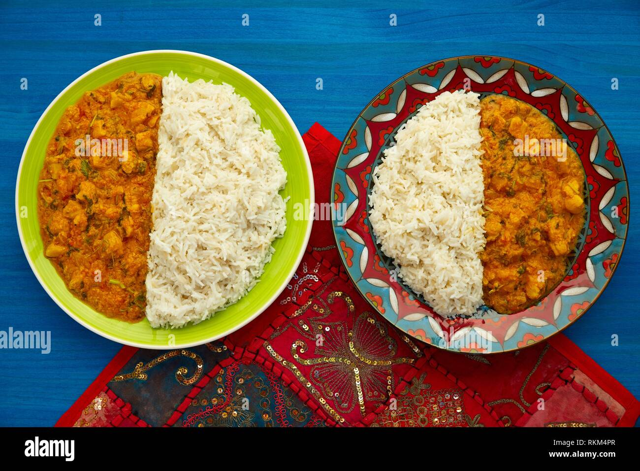 Chicken curry dish indian recipe on blue table. - Stock Image
