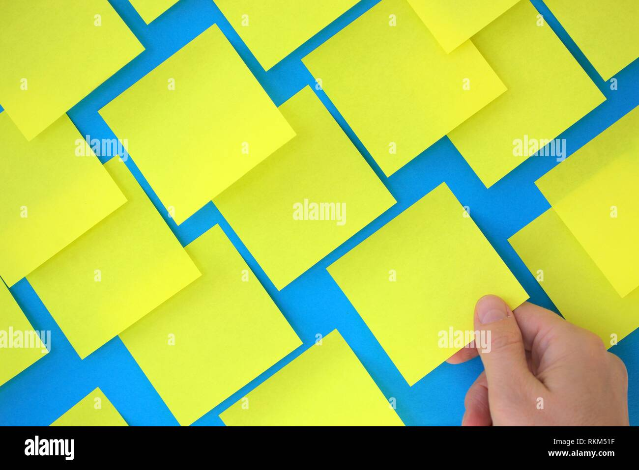 Hand holding post-it note on blue board. - Stock Image